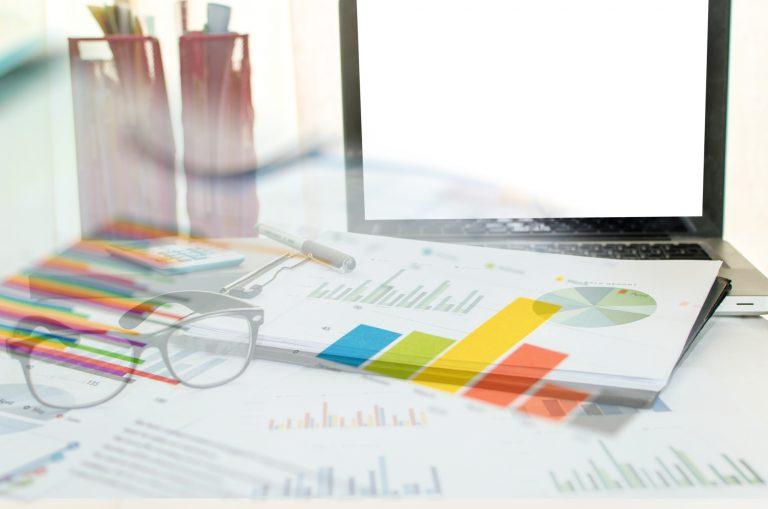 Mesa com papéis com gráficos, um computador e um par de óculos