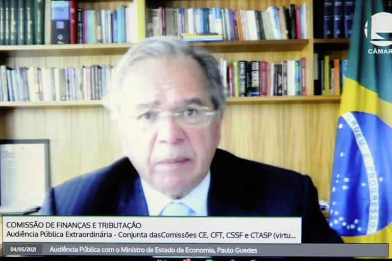 Ministro Guedes fala olhando para a tela do computador. Atrás dele há uma estante de livros e uma bandeira do Brasil